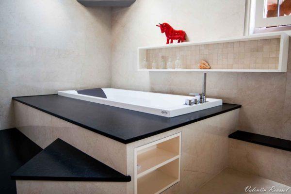 une baignoire balnéo entourée de granit et grès imitation marbre