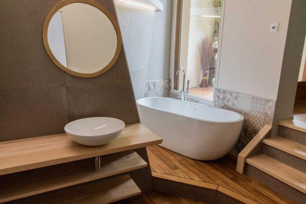 Salle de bain allure bois et pierre avec vasque et baignoire îlot et lignes épurées.