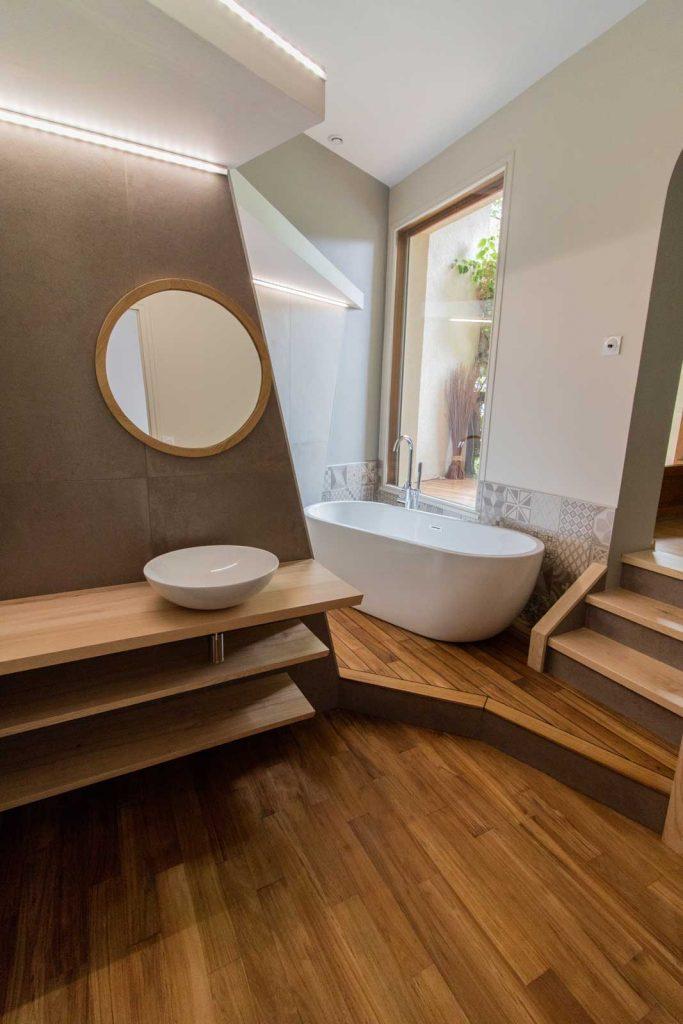 Salle de bain allure bois et pierre avec vasque et baignoire minimaliste et lignes épurées.