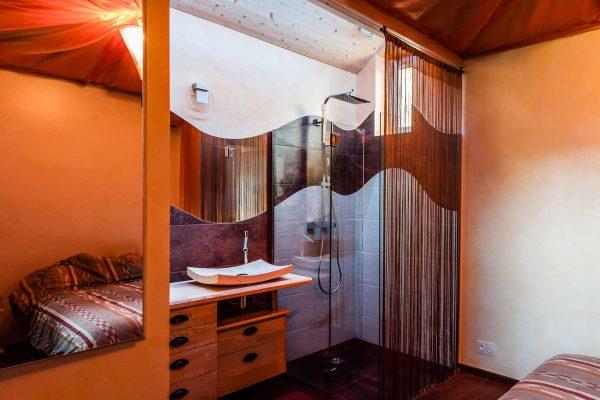 Suite parentale avec une salle de bain privée équipée d'une douche italienne.