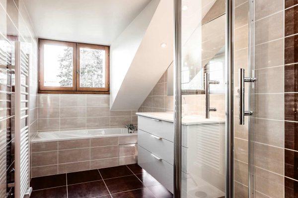 Simplicité et élégance pour cette salle de bain bicolore équipée d'une douche et d'une baignoire.