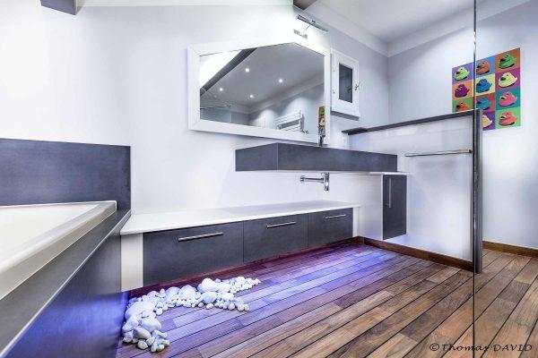 Baignoire et rangements de salle de bain ingénieux pour cet aménagement de salle de bain moderne.
