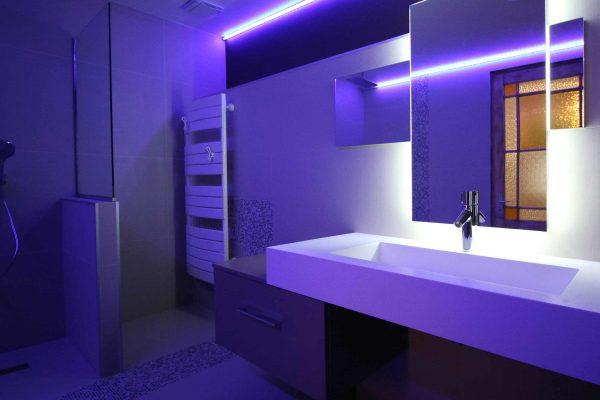 Jeu de lumière sur le lavabo pour une salle de bain moderne.