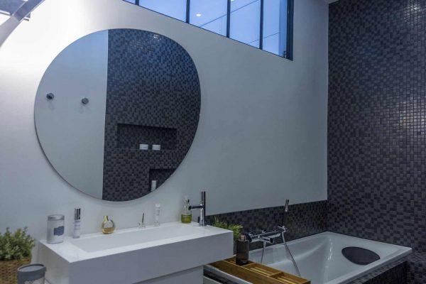 Salle de bain aménagée dans un style rétro chic par Ar Intérieur : mise en valeur de la verrière.
