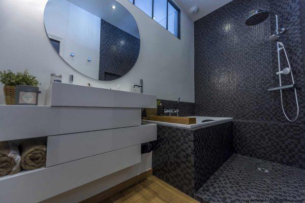 Une salle de bain rétro carrelée d'une mosaïque en duo de gris.