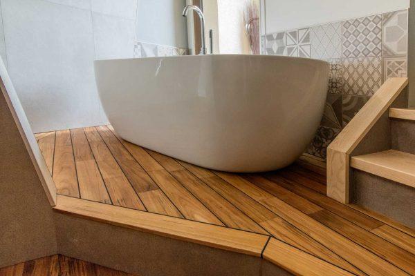 La baignoire se met en scène sur une estrade en bois.