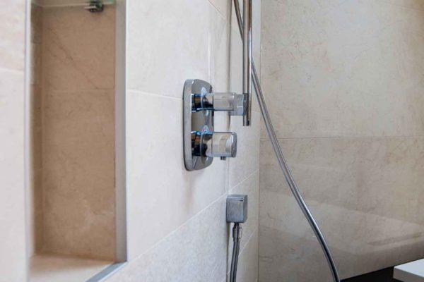 une robinetterie de douche encastrée avec une niche