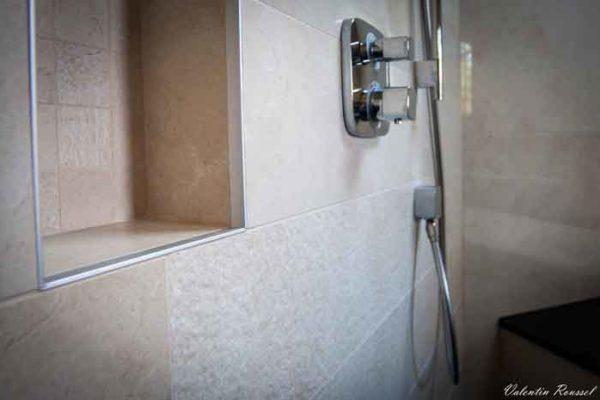 Une robinetterie de douche encastrée avec une niche de rangement pour gels douche.