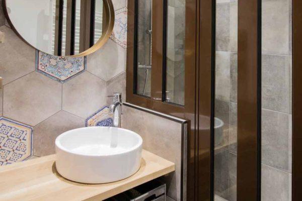 une salle de bain industrielle avec une paroi de douche en alu et miroir laiton rond