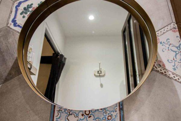 carrelage hexagonal avec un miroir laiton pour une salle de bain industrielle