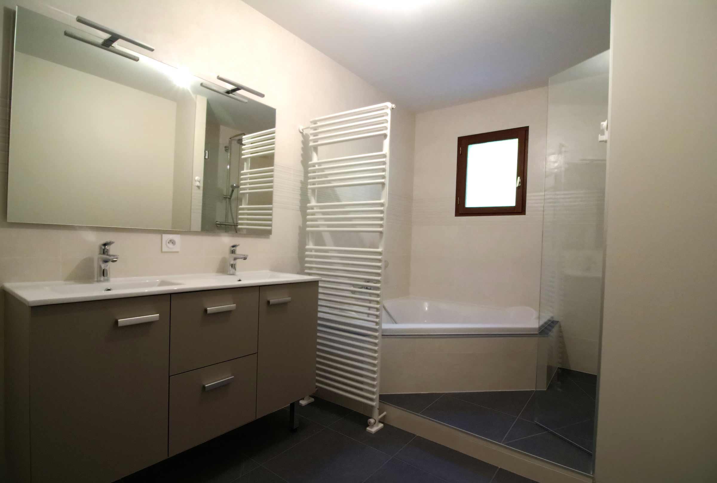 baignoire d'angle avec un sèche serviette en claustra et une douche à l'italienne.