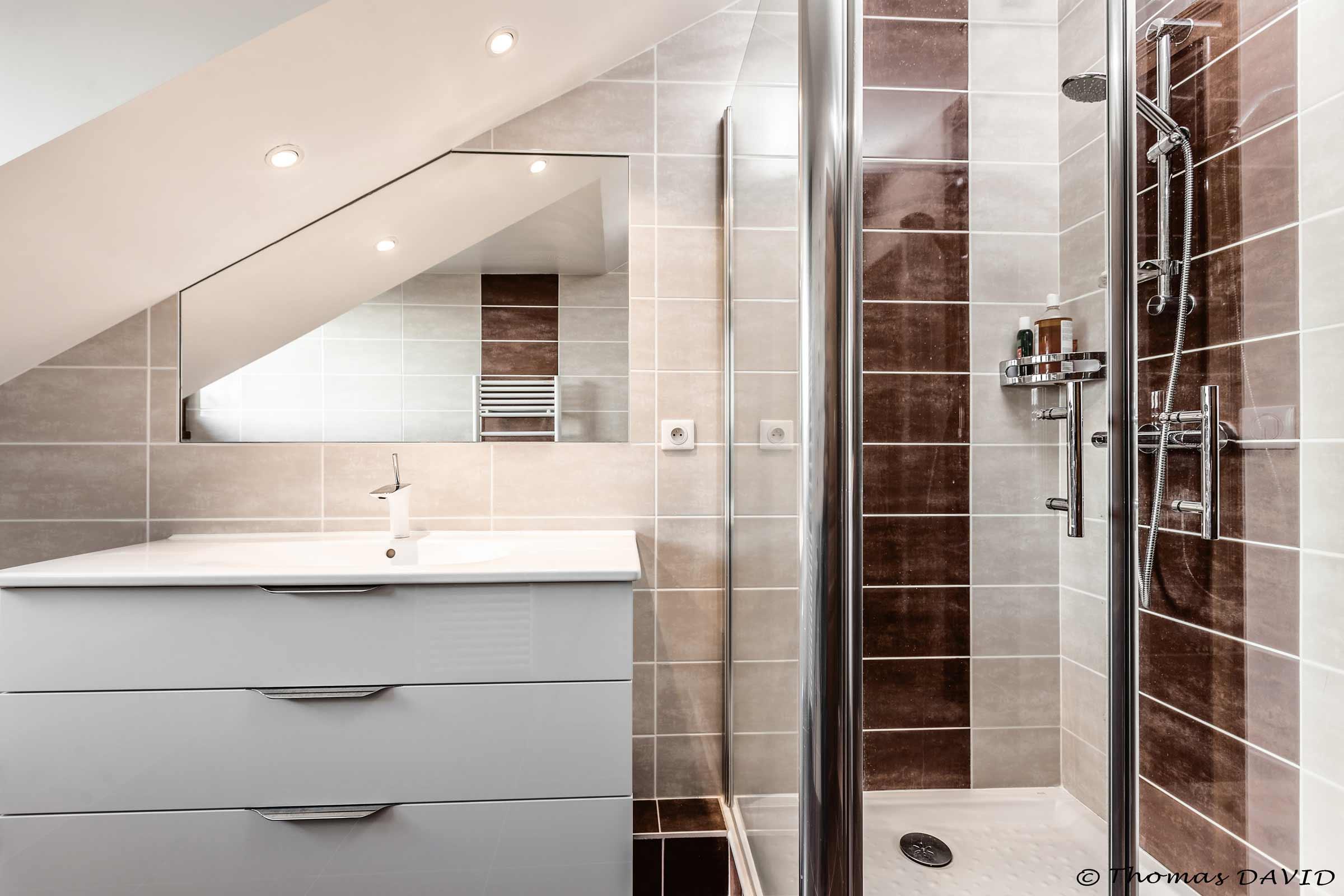 Une cabine de douche sous les toits avec un miroir coupé sur mesure.