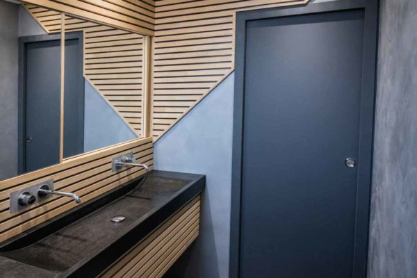 Un lattis en bois pour cette magnifique rénovation de salle de bain avec lavabo en granit et béton ciré.