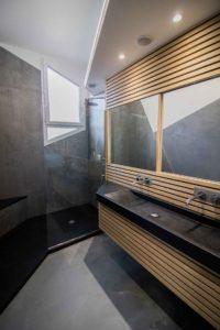 Une belle douche à l'italienne en granit noir assorti au lavabo.
