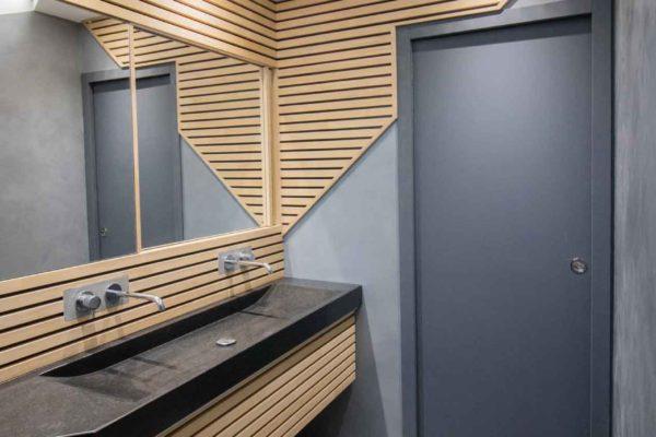 Une salle de bain moderne en bois ciré, lattis bois, lavabo en granit noir.