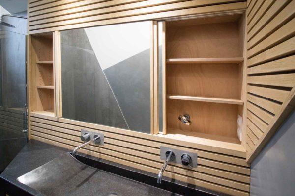 Un placard dissimulé derrière des miroirs coulissant pour cette salle de bain avec un lattis en bois.