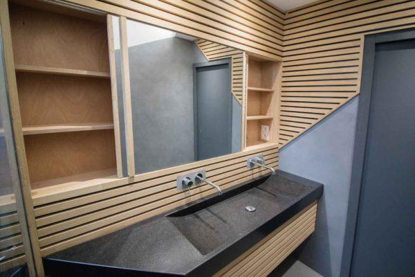 Un placard caché derrière des miroirs coulissant avec un lavabo en granit noir et de la robinetterie encastrée.