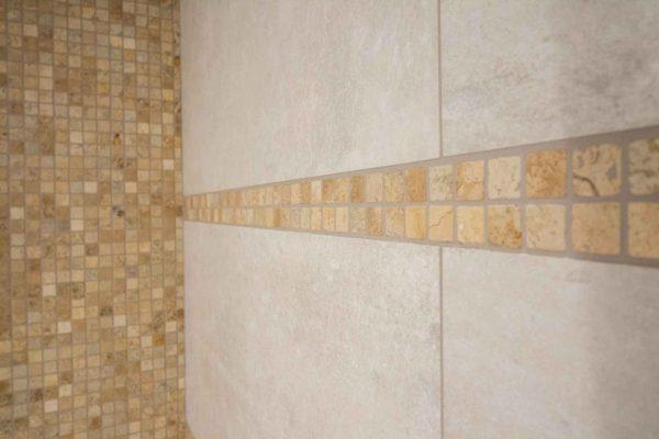 Une frise qui rejoint un mur entier de mosaique entourée par du carrelage grand format utilisé dans la rénovation de cette salle de bains.