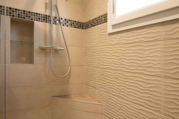 Une niche pour gel douche pour cette douche à l'italienne avec son banc en angle.