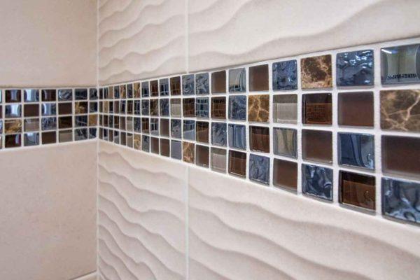 De la mosaique en frise entouré de faience rectangulaire à effet de vagues.