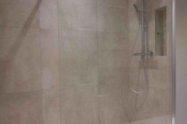 Une douche à l'italienne en mosaique assorti aux grands carreaux muraux et une paroi de douche simple.