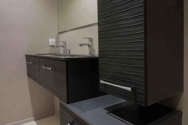 Meuble lavabo suspendu noir avec un plan de toilette en verre noir et colonne de rangement, une rénovation sur Grenoble.