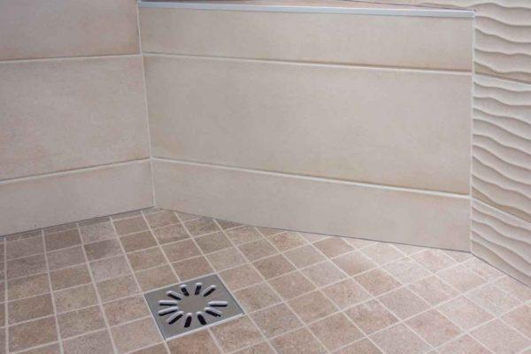 un banc d'angle dans une douche à l'italienne dans le cadre d'une rénovation de salle de bains.
