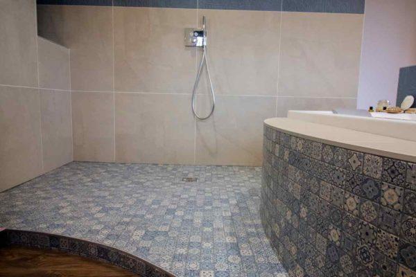 un receveur de douche italienne habillé en mosaïque dans une suite parentale
