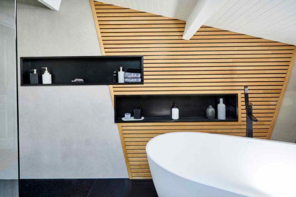 Des niches pour gel douche en granit avec une baignoire ilôt conçu par les artisans ar'interieur.