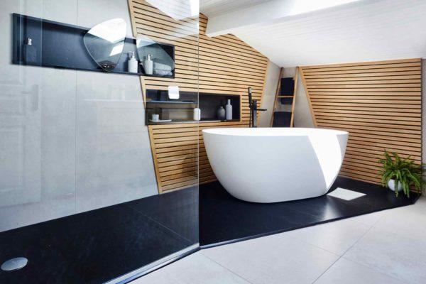 une baignoire ilôt sur un sol en granit dans une salle de bains fraîchement rénovée.