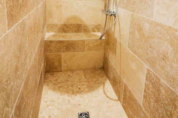 Une douche italienne en mosaïque de travertin
