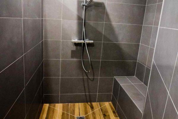 Une douche italienne en pointe de diamant imitation bois et faience gris foncée, une salle de bain ar'interieur