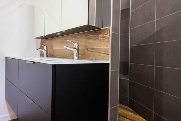 Meuble lavabo noir mat avec carrelage imitation parquet et gris foncé.