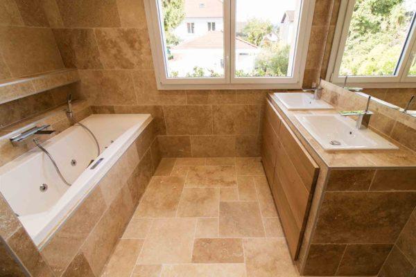 Une baignoire balnéothérapie et un meuble lavabo avec vasques encastrées dans une salle de bains en travertin