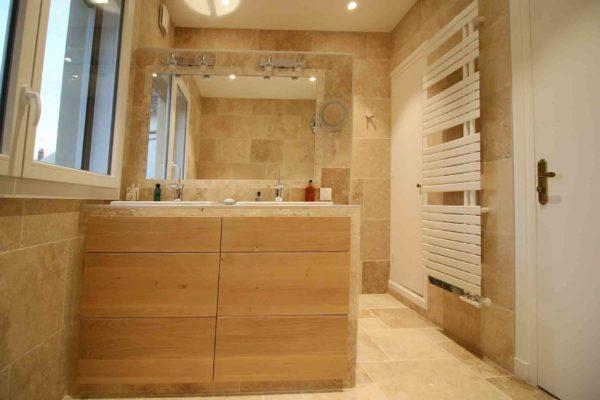 Un meuble sur mesure en chêne dans une salle de bains en travertin