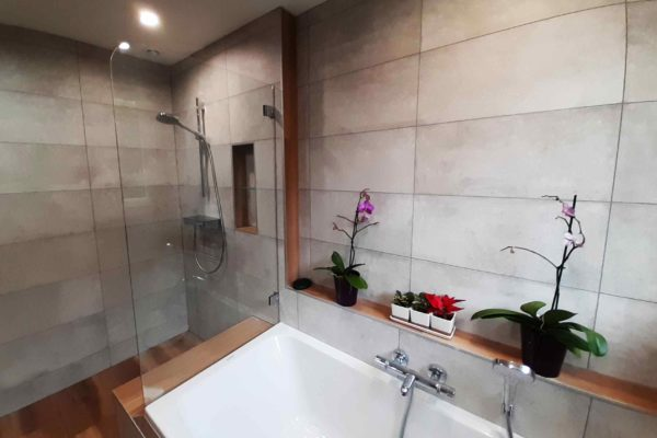 Une douche accolée à la baignoire avec une niche pour gels douche.