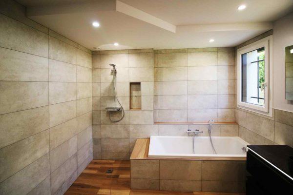 Rénovation d'une salle de bain mettant en valeur agencement de la douche avec la baignoire.
